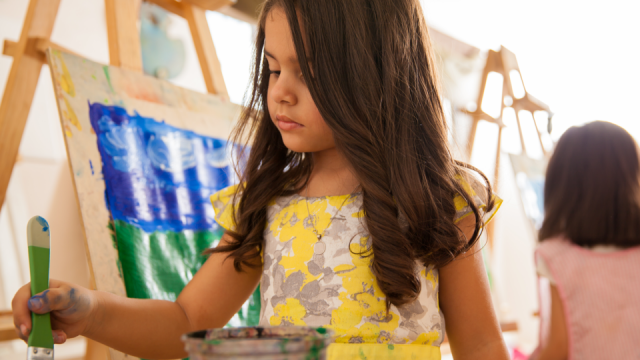 A young girl paints.