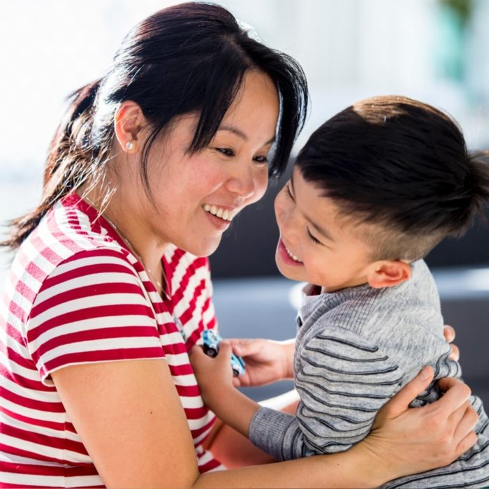 A woman laughs with her toddler son.