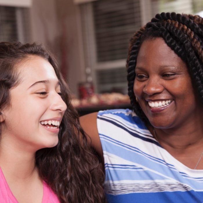 A woman laughs with her foster child.