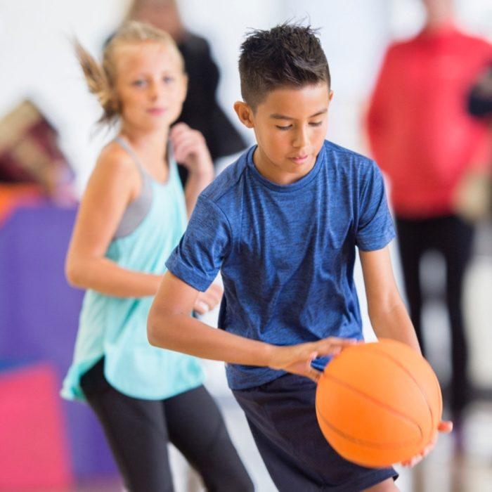 A boy bounces a basketball.