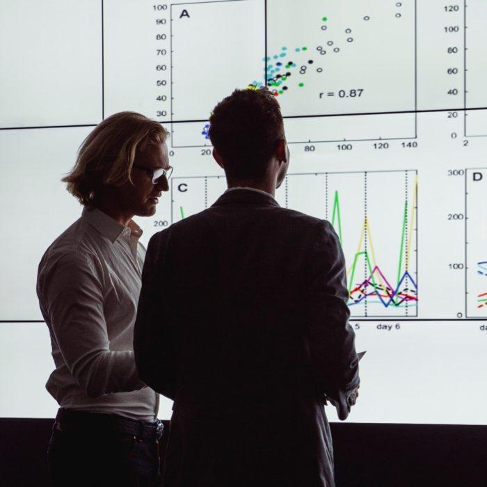Two men look at large screens of data.